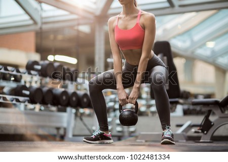 Fit young woman squatting while standing on the floor and holding heavy kettlebell between legs during training #1022481334