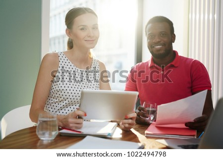 Happy young office staff in casualwear looking at camera with smiles while working over project #1022494798
