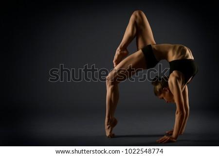 Yoga Backbend Gymnastics, Woman Acrobat in Back Bend Pose, Girl Gymnast Strong Flexible Body over Black Background #1022548774
