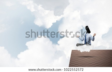 Faceless businessman with camera zoom instead of head sitting in lotus pose #1022552572