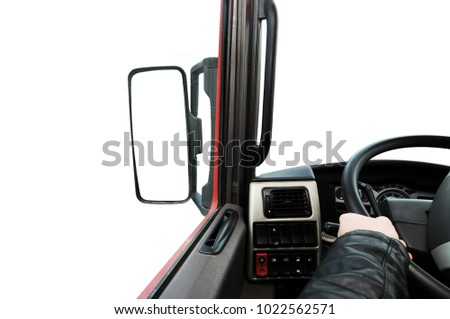 Truck dashboard with driver's hand on the steering wheel and side rear-view mirror against isolated on a white background #1022562571