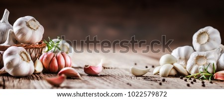 Garlic banner. Garlic bulbs on wooden rustic table in panorama shape. A pile of garlic peeled cloves.  #1022579872