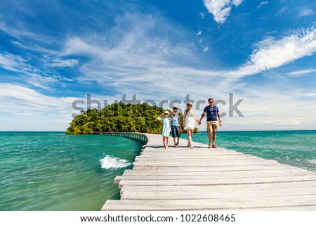 Family walking on wooden pathway leading to beautiful tropical island in Cambodia #1022608465