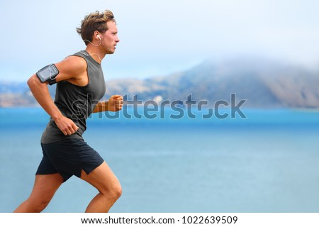Running app on smartphone. Male runner listening to music jogging with armband for smart phone. Fit man fitness model working outdoor by water. #1022639509