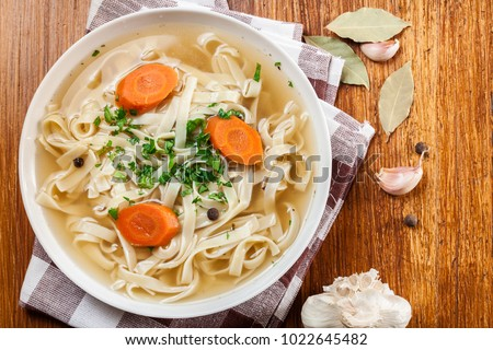 Tasty meat broth with noodles, carror and parsley in a plate. Top view #1022645482