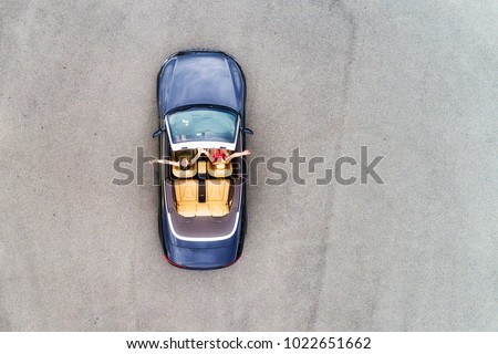 Small passenger sports convertible car with soft top down and happy couple of young women enjoying lifestyle and freedom in aerial top down view. #1022651662