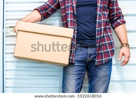 Young man holding a moving cardboard box in front of a storage door.Life style, storage, moving, storing, organizing concept. Space to write #1022658016