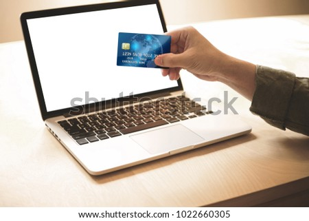 Payment online Concept .Man holding credit card and payment or shopping online whit blank computer screen. #1022660305