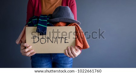Donation Concept. Woman holding a Donate Box with full of Clothes Royalty-Free Stock Photo #1022661760