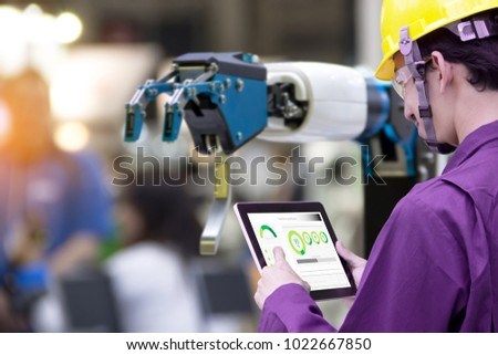 Industry 4.0 Robot concept .Engineers use laptop computers for machine maintenance, automation tools, robot arm at the factory.   #1022667850