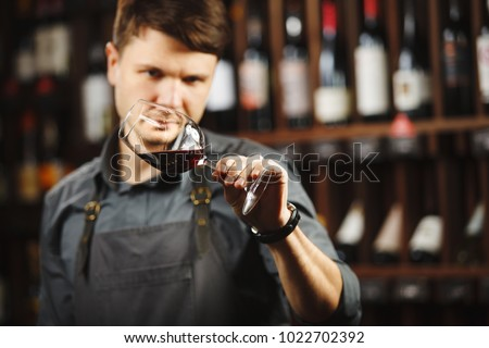 Bokal of red wine on background, male sommelier appreciating drink #1022702392
