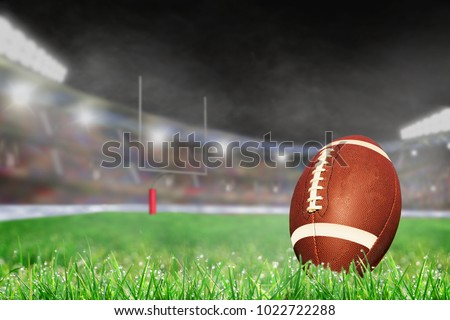American football on field grass in brightly lit outdoor stadium with focus on foreground and shallow depth of field on background. Deliberate lens flare and copy space.