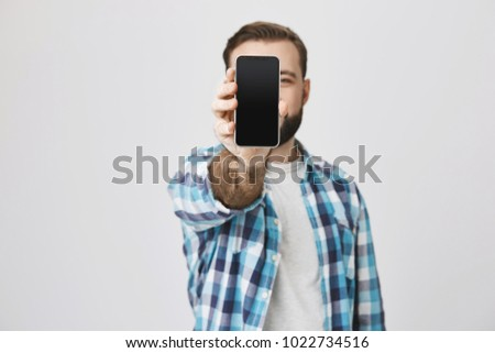 Male model with beard and trendy haircut in checked shirt showing smartphone at camera covering face with it, standing against gray background. Consultant shows gadget to customer of shop he works at #1022734516