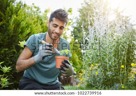 Close up of mature bearded caucasian man in blue t-shirt planting flowers in pot with garden tools,spending peaceful morning in garden hear house. #1022739916