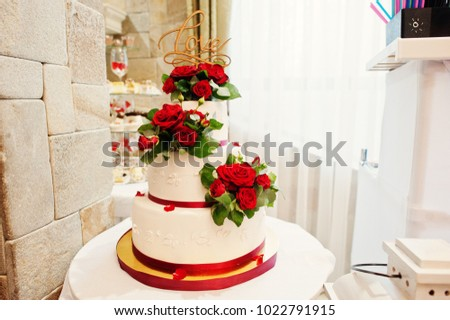 Close-up photo of a big white and red wedding cake decorated with fresh red roses.