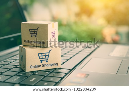 Online shopping / ecommerce and delivery service concept : Paper cartons with a shopping cart or trolley logo on a laptop keyboard, depicts customers order things from retailer sites via the internet. #1022834239