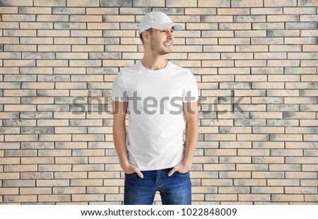 Young man in stylish t-shirt against brick wall. Mockup for design #1022848009