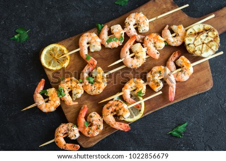 Grilled shrimp skewers. Seafood, shelfish. Shrimps Prawns skewers with herbs, garlic and lemon on black stone background, copy space. Shrimps prawns brochette kebab. Barbecue srimps prawns. #1022856679