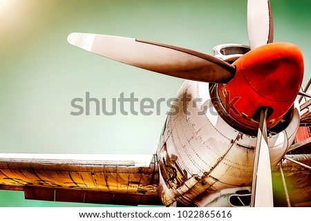 Old airplane turboprop engine with propeller blades, parts of wings and aircraft fuselage - concept closeup  historic vintage plane travel flight dramatic look retro style propeller plane aircraft #1022865616