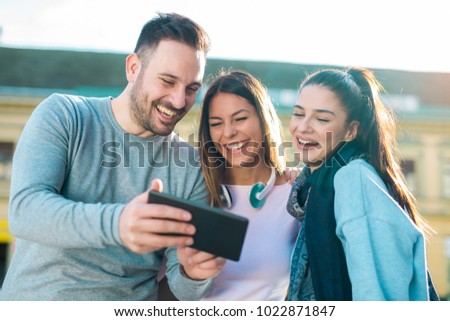 Group of smiling friends with digital tablet outdoor #1022871847