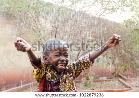 Water is coming! African ethnicity little boy happy to finally get some rain #1022879236