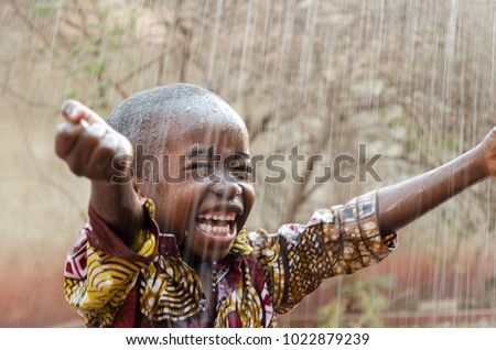 Little Native African Boy Standing Outdoors Under the Rain (Water for Africa Symbol) #1022879239