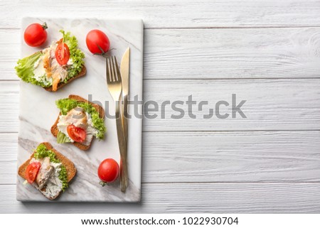 Marble board with tasty chicken bruschettas on wooden table #1022930704
