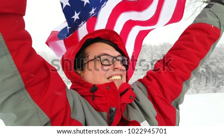 Man waving a flag of the united states in winter on a ski slope #1022945701