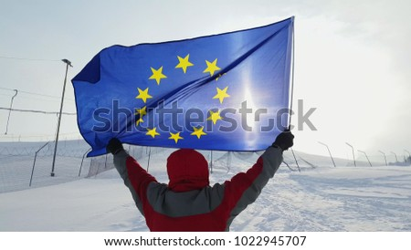 Man waving a flag of the European Union in winter on a ski slope #1022945707