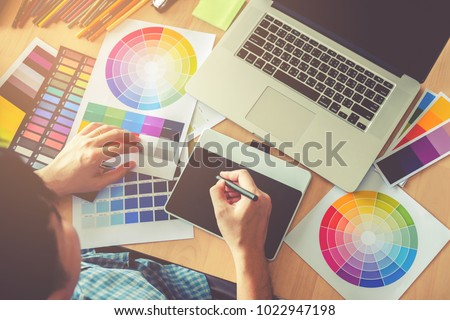 Graphic designer drawing on graphics tablet at workplace #1022947198