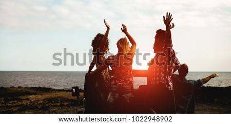 Silhouette of happy tourists friends doing excursion next the beach on convertible 4x4 car - Young people having fun traveling together - Friendship and vacation concept - Focus on center guys #1022948902