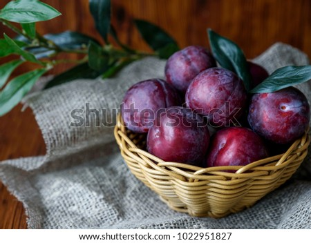 Plum. Fresh plum. Harvest. Autumn harvest. Autumn. Blue plums. Yellow plum. Fresh plums on a wooden surface. Fresh plums on wooden table background. #1022951827
