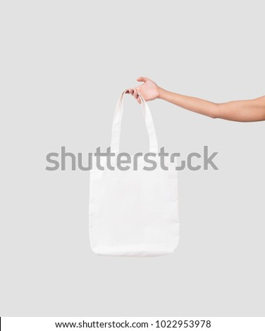 hand holding bag canvas fabric for mockup blank template isolated on gray background.  #1022953978