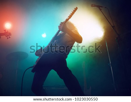 Rock band performs on stage. Guitarist, bass guitar and drums. Scene, light. #1023030550