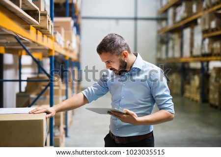 Man warehouse worker with a tablet. #1023035515