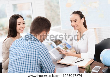 A young man and a woman came to the travel agency. They want to go on a trip during their holidays. The girl agent offers them different countries. She shows it in the booklet. #1023047974