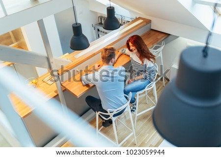 Beautiful couple talking in their pristine home #1023059944