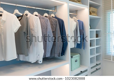 modern wooden wardrobe with clothes hanging on rail in walk in closet  #1023082888