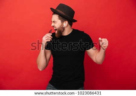 Image of joyous guy wearing black t-shirt and hat singing and listening to music with cell phone and wireless earphones isolated over red wall #1023086431