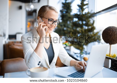 young smiling caucasian business woman talking on the phone while working at the laptop in the cafe #1023104860