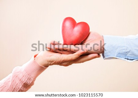 Elderly care concept. Young male doctor from health care facility passing a heart shape figure to senior woman. Close up of hands holding abstract love sign in nursing home. Background, copy space. #1023115570
