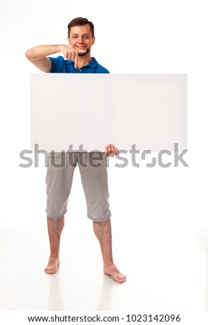 A guy with a beard posing with a white sign. Shows different emotions. Isolated on a white background. In a gray trousers and a blue T-shirt. For advertising, logo, business cards, contact phones, etc #1023142096