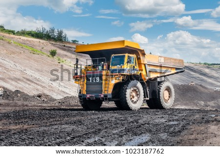 Big dump truck or Mining truck is mining machinery, or mining equipment to transport coal from open-pit or open-cast mine as the Coal Production. This picture show dump truck on open-pit coal mine. #1023187762