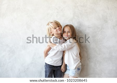 Two Caucasian siblings brother and sister posing for picture during family photo shooting: stubborn blonde boy doesn't want to embrace his little sister, grimacing and hiding arms behind his back