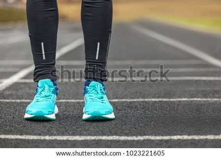 Woman's legs in blue colored running shoes standing on asphalt. #1023221605