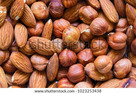 Nuts pile background. Cashew, almond, hazelnut mix closeup. Organic food rustic banner template. Tasty healthy snack. Scattered nut on table top view. Nut assortment flat lay. Nut texture. Nut package #1023253438