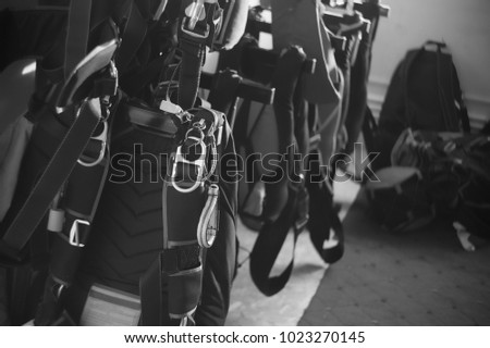 Sport parachutes, packed before jumping, are stored in a parachute packing room. Parachute equipment.Black and white. Stylization under the photo made on black-and-white film. #1023270145