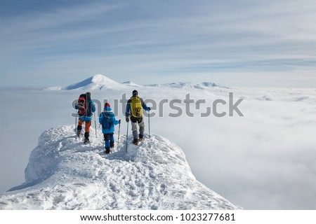 Three hikers with backpacks are on a high snow-covered peak above the clouds in the mountains. They rest after a heavy ascent, enjoying an incredible view. #1023277681