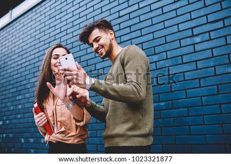 Cheerful best friends viewing funny photos in social networks via smartphone standing together on street, happy male and female hipsters watching funny online video content on mobile phone outdoors #1023321877