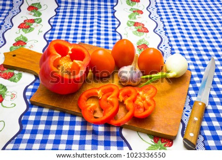 Cutting board with a knife, chopped peppers, tomatoes, onions, garlic on a blue tablecloth #1023336550